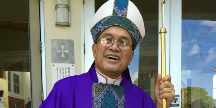 This November 2014 photo shows Archbishop Anthony Apuron standing in front of the Dulce Nombre de Maria Cathedral Basilica in Hagatna, Guam. The Vatican administrator appointed to temporarily oversee the Catholic church in Guam has arrived on the island while an investigation is underway into allegations that Apuron sexually assaulted young boys over several decades. Pope Francis named Archbishop Savio Tai Fai Hon on Monday, June 6, 2016 to take over the Agana archdiocese and he is expected to remain in Guam until his mission to stabilize the local church is met. (AP Photo/Grace Garces Bordallo)